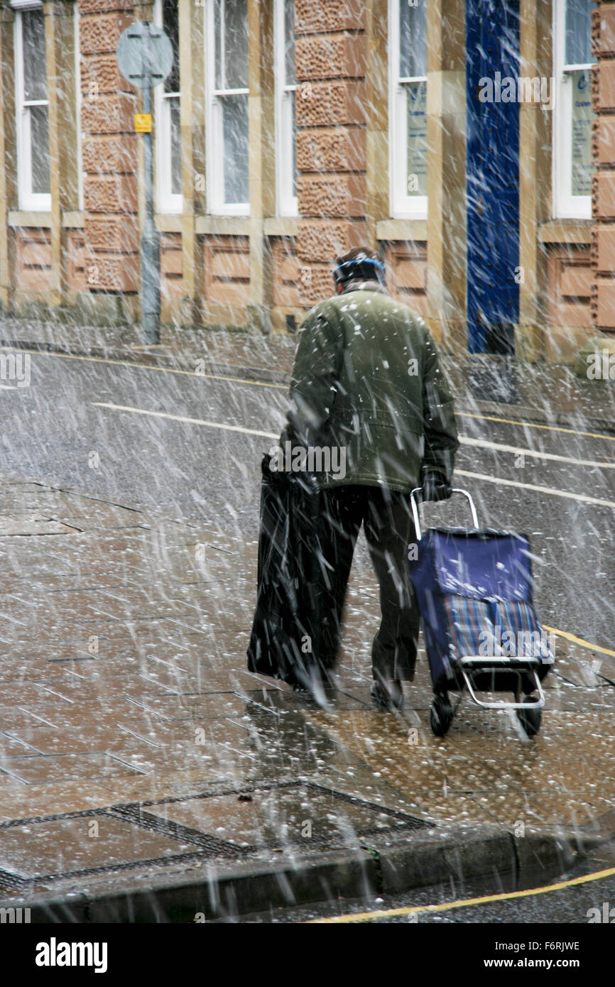Snowing man walking in snow bad weather pulling shopping trolley UK England winter - Stock Image