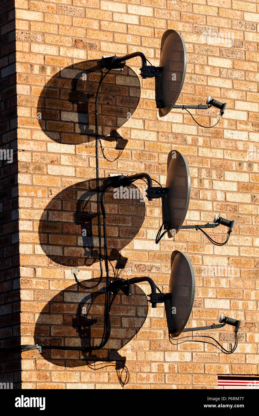 Three Sky TV digital Satellite dishes together attached vertically above each other on a modern house wall in Dundee, - Stock Image