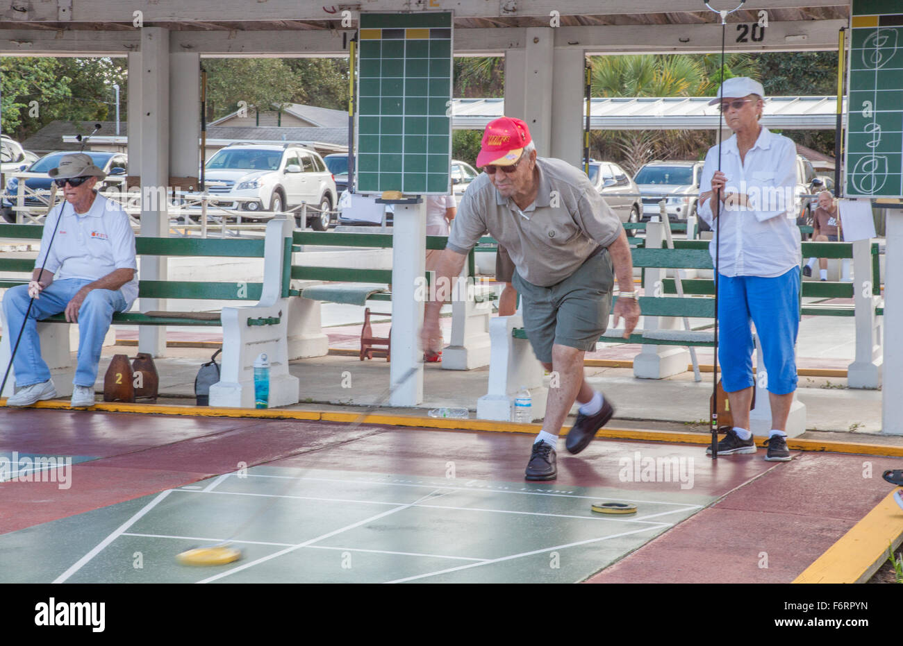 Senior citizens playing competitive shuffleboard game in Flager Ave in New Smyrna Beach Florida - Stock Image