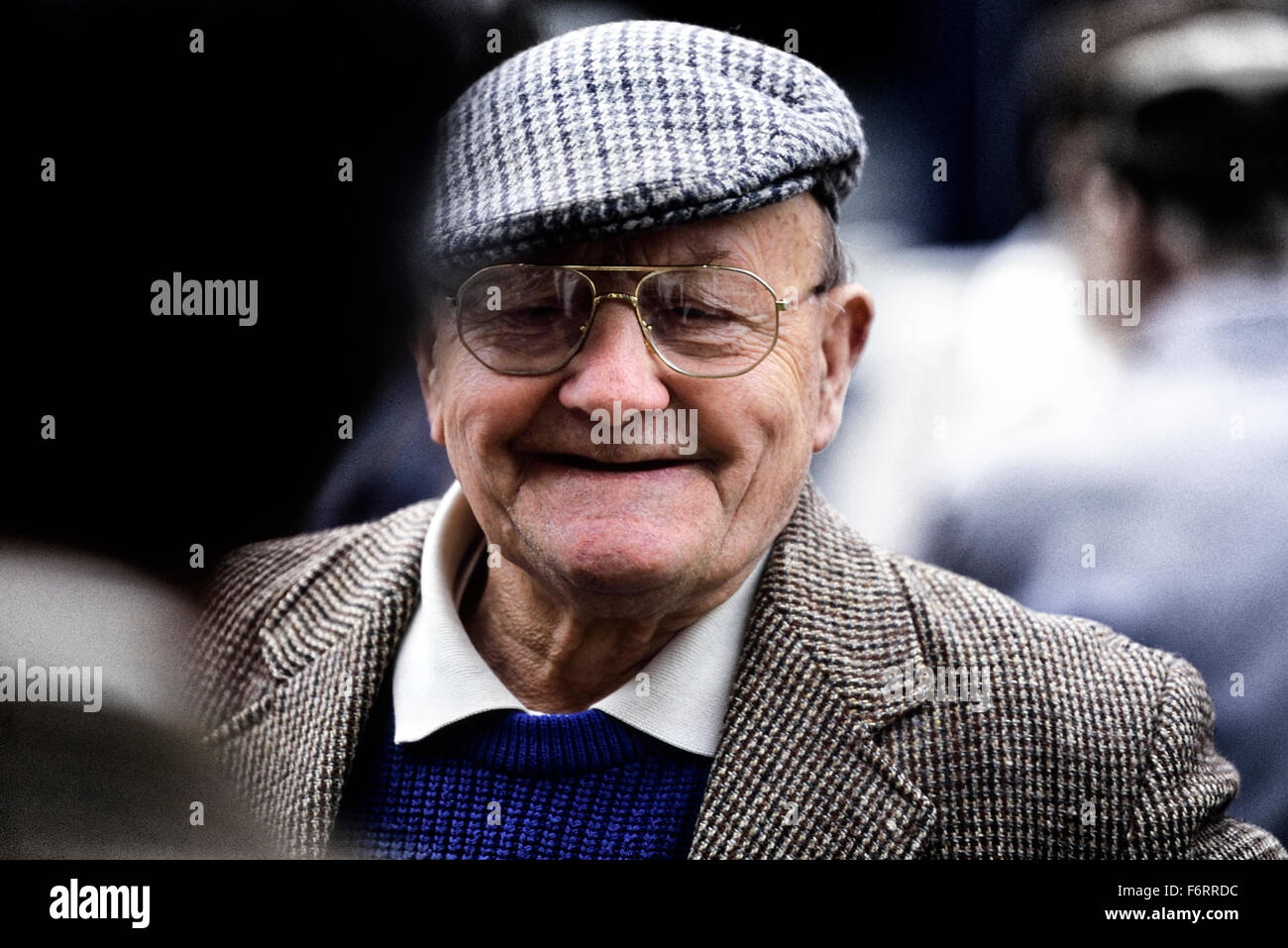 A smiling old gentleman wearing a tweed cloth cap and jacket - Stock Image
