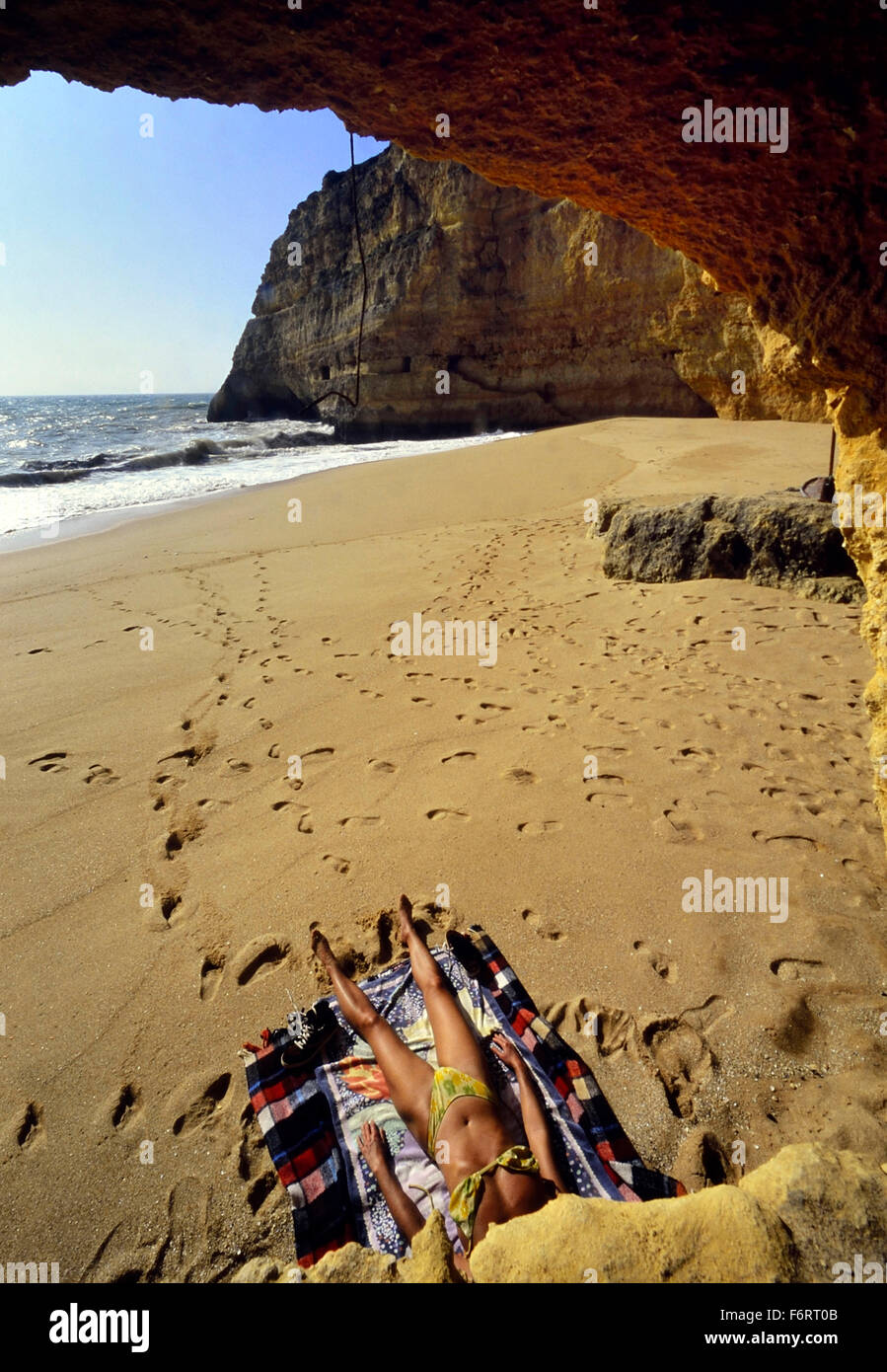 A female sunbather on a deserted beach near Albufeira, The Alarve. Portugal. Europe - Stock Image