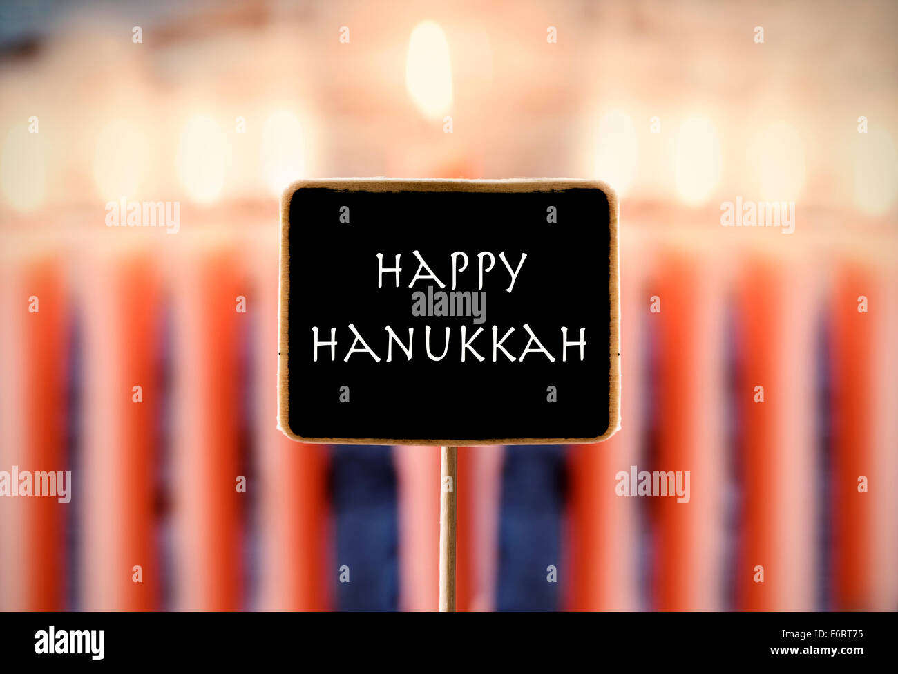 closeup of a chalkboard with text happy Hanukkah and a menorah with nine lit candles in the background - Stock Image