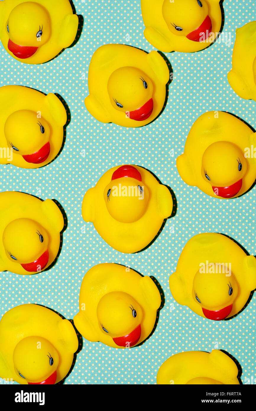 a pile of rubber ducks, one of them countercurrent, on a dot-patterned background, with a hard-shadow processing - Stock Image