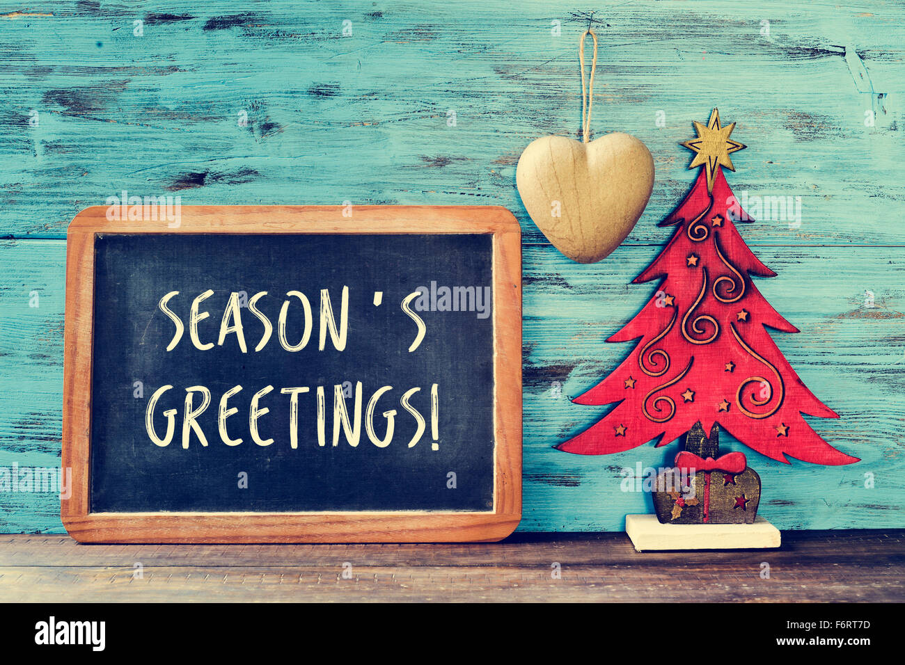 Seasons greetings christmas stock photos seasons greetings a chalkboard with the text seasons greetings written in it and a rustic wooden christmas tree m4hsunfo