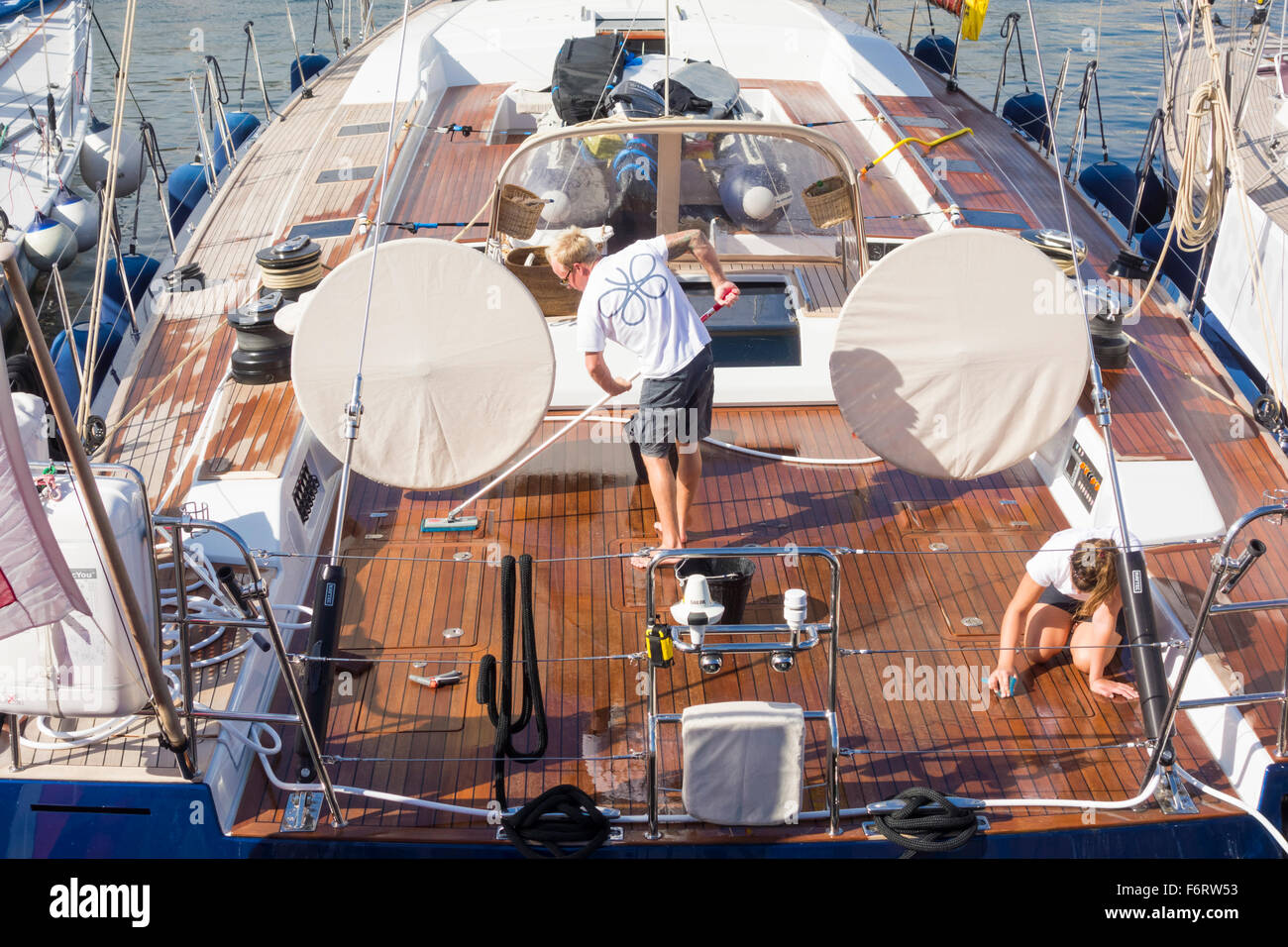 Young male and female crew members scrubbing deck of luxury yacht - Stock Image