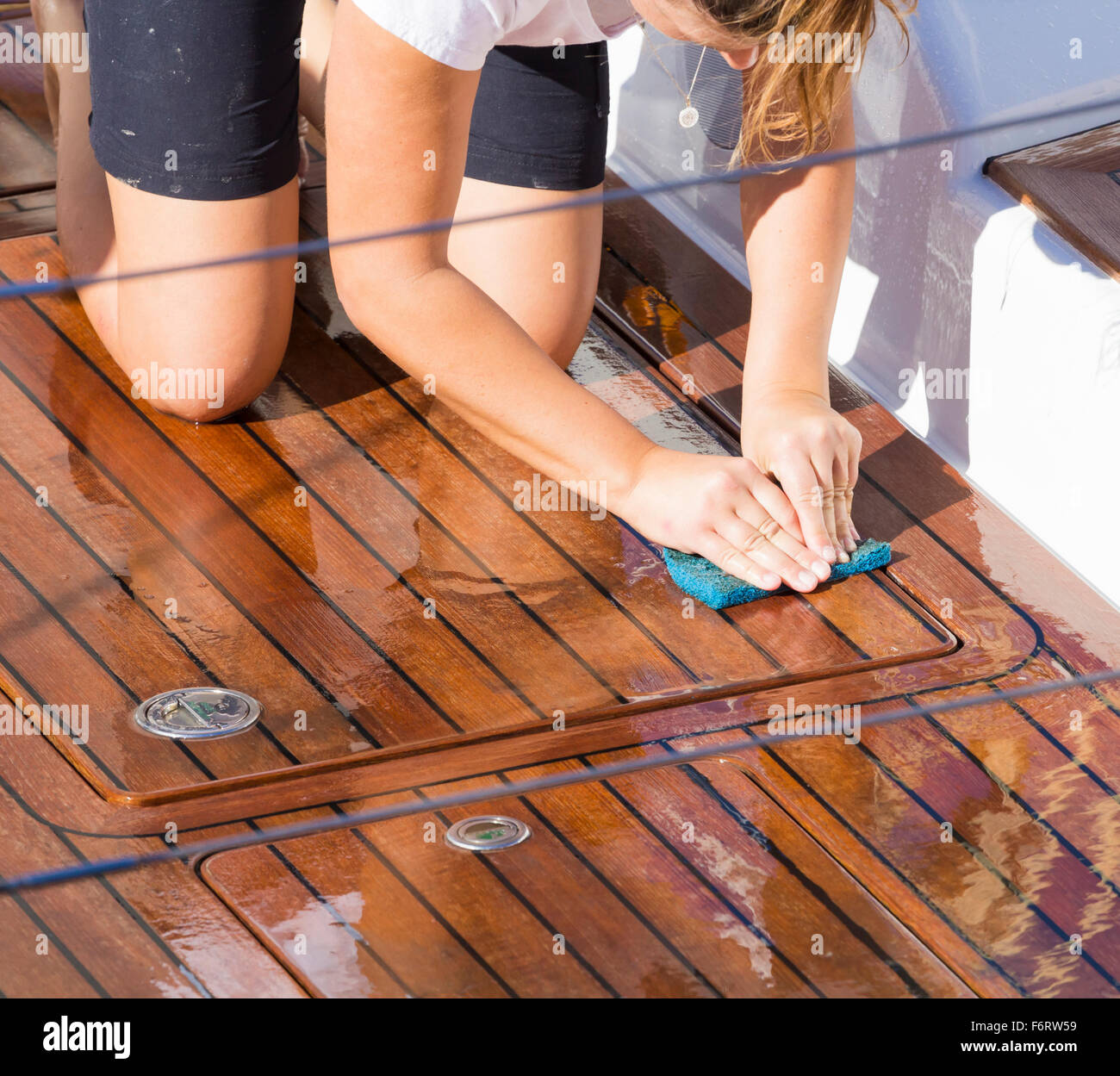 Young female crew member scrubbing deck of luxury yacht - Stock Image