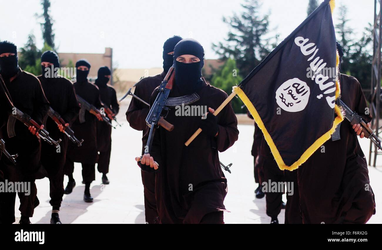 Islamic State of Iraq and the Levant propaganda photo showing masked militants holding the ISIS black banner of Stock Photo