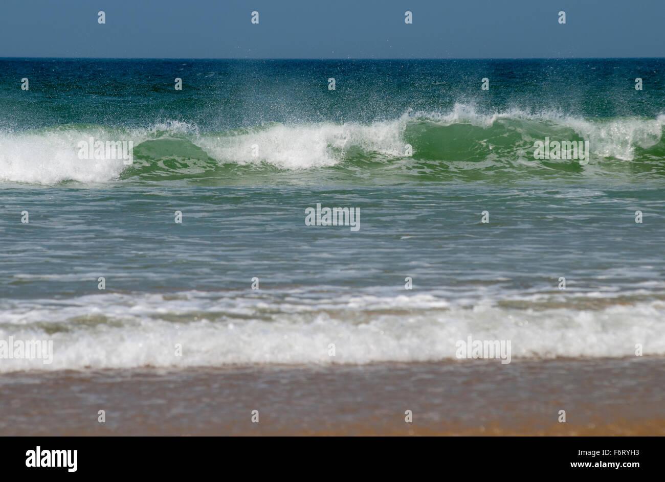 Waves crashing onto a beach in Cornwall, England, UK - Stock Image