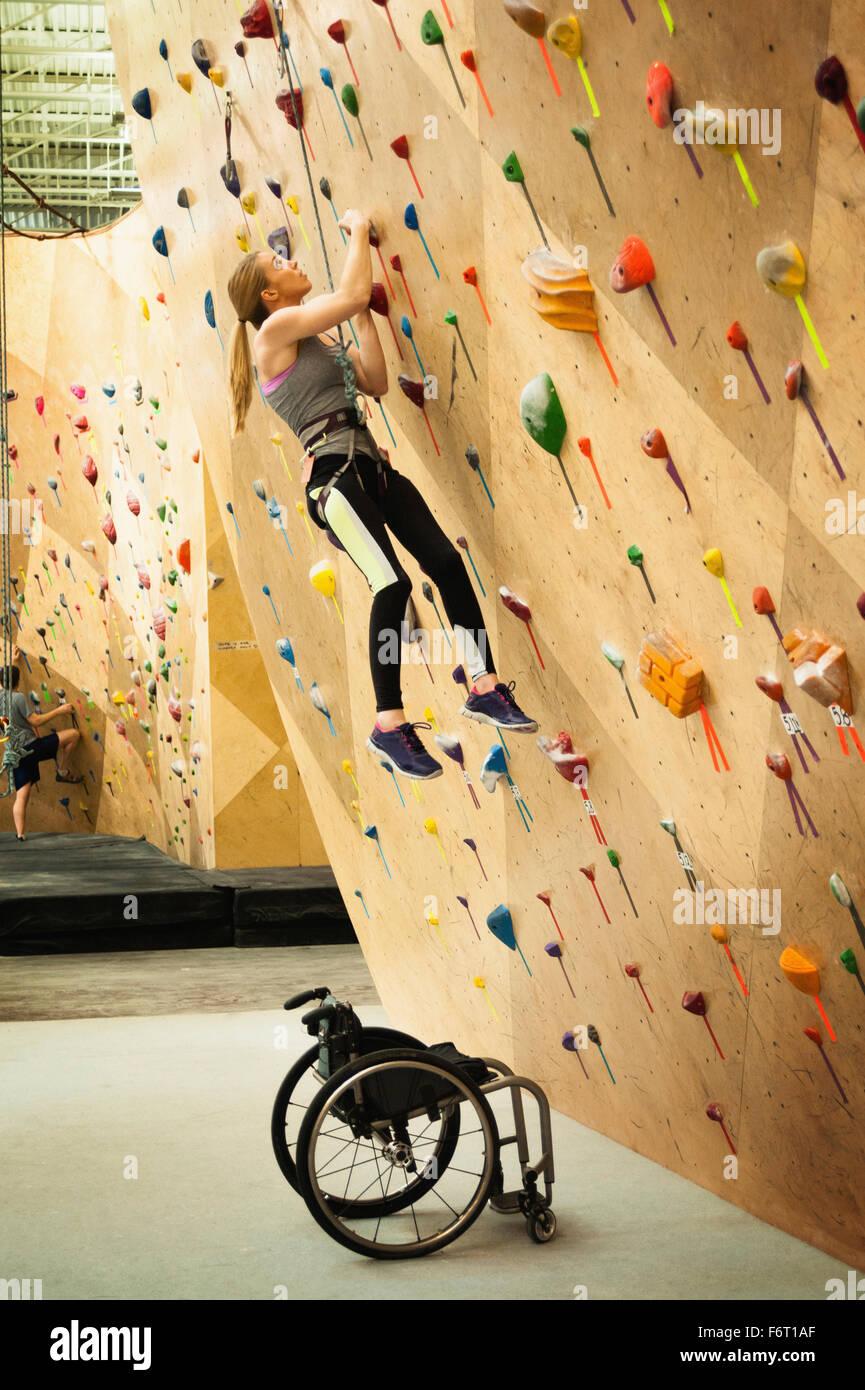 Paraplegic woman rock climbing in gym Stock Photo