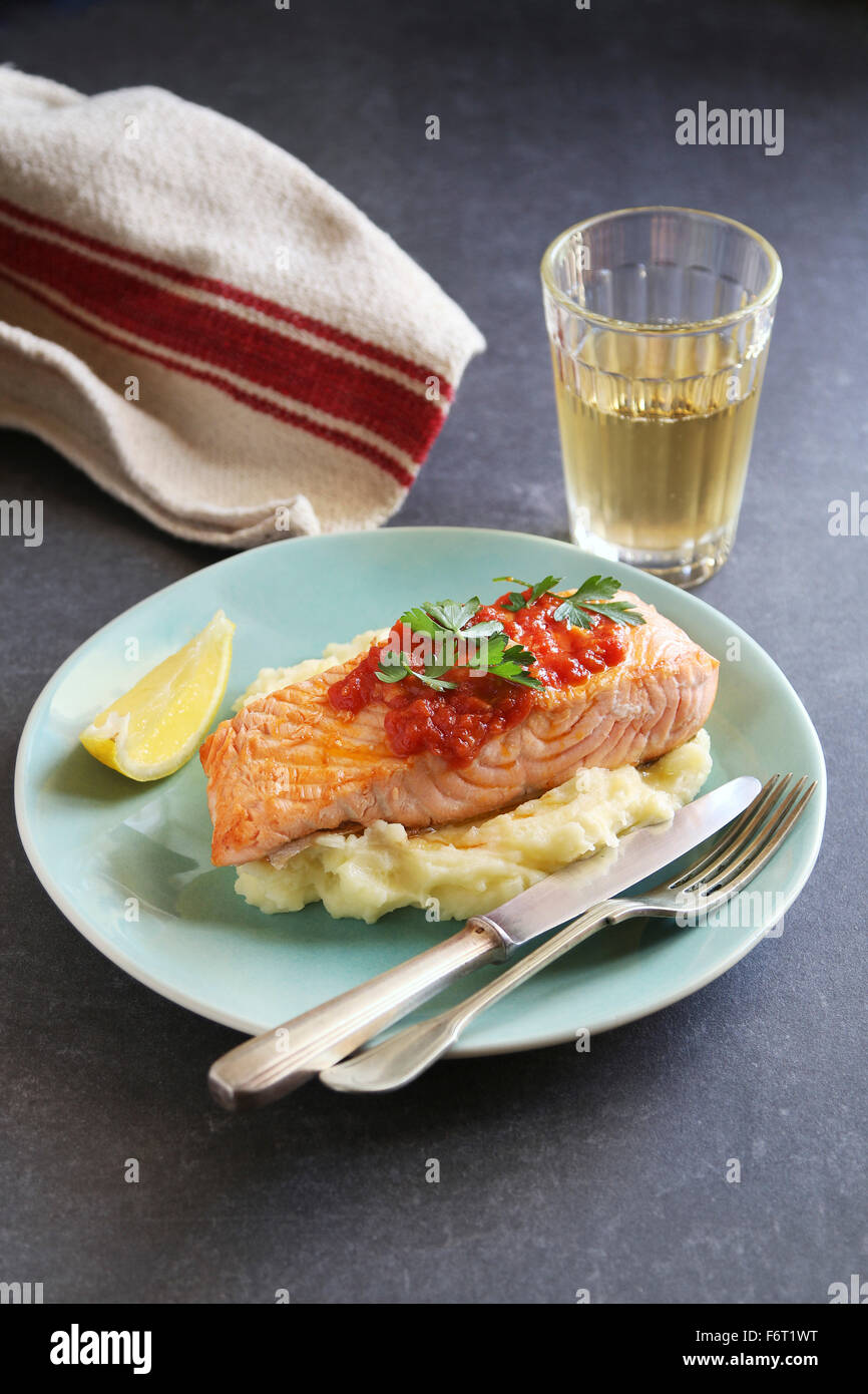 Fried salmon steak with mashed potatoes and garlic tomato sauce - Stock Image
