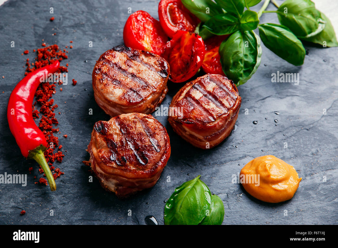 Grilled meat fillet steak wrapped in bacon medallions - Stock Image
