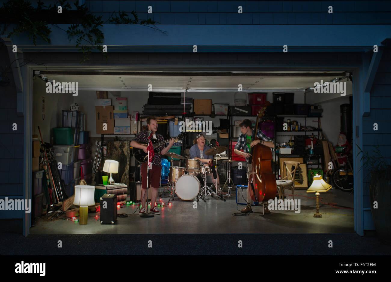 Caucasian band playing in garage - Stock Image