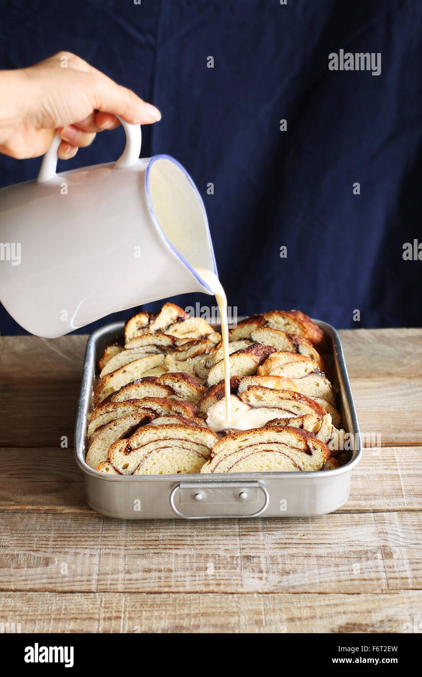 Preparing bread pudding.Pouring egg mixture over slices of brioche bread in a pan - Stock Image