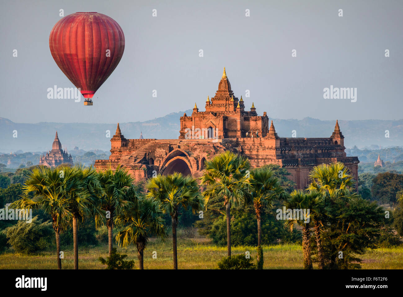 Hot air balloon flying over temple - Stock Image