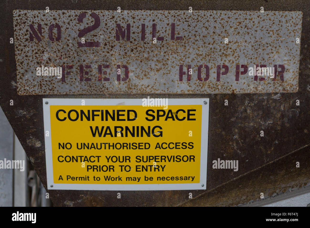 A confined space warning sign on an industrial mill hopper - Stock Image