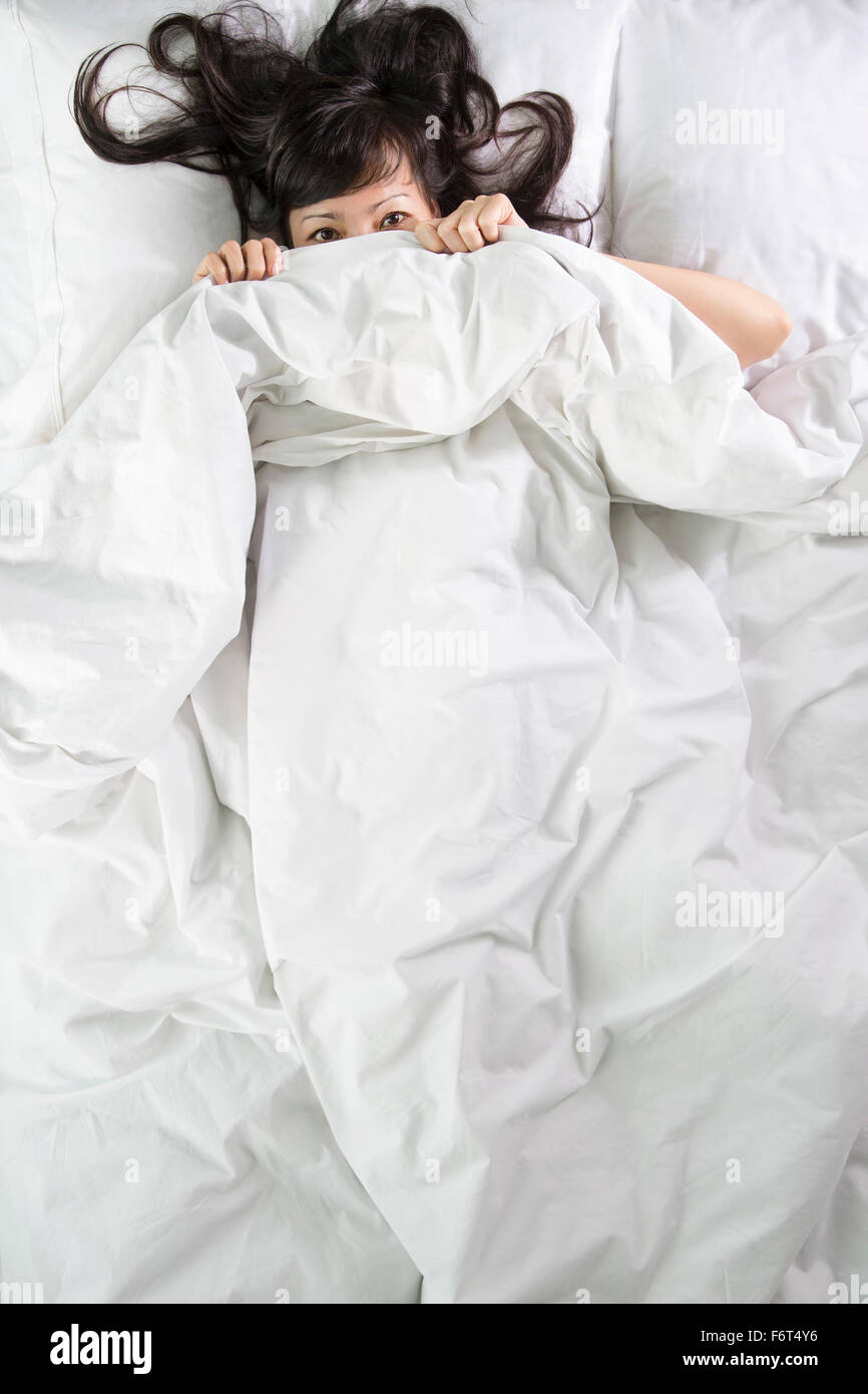 Mixed race woman peeking out from bed blankets Stock Photo