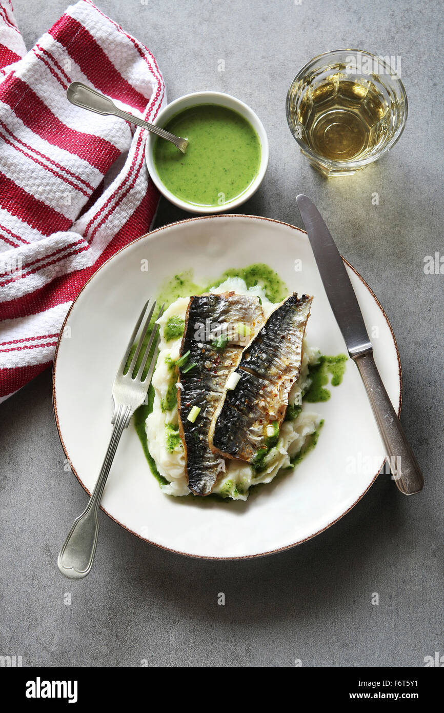Two fillets of grilled mackerel fish on a plate with mashed potatoes and salsa verde.Top view - Stock Image