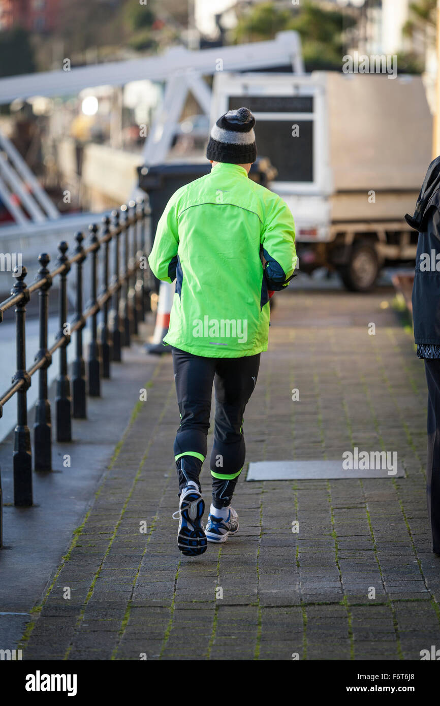 An older man wearing a woolly bobble hat, tracksuit bottoms and a green hi-viz top runs away from the camera on - Stock Image