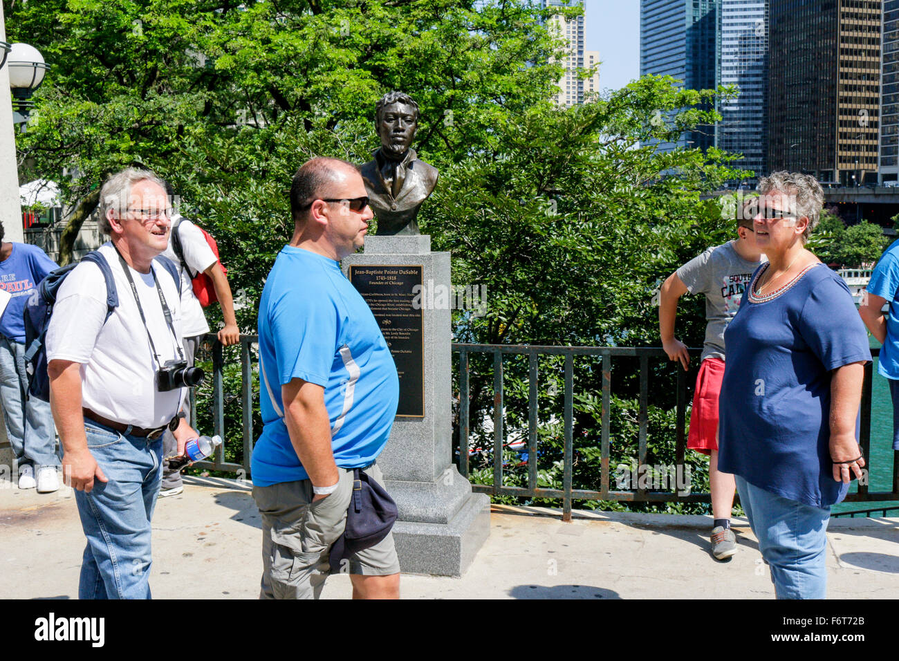 Tourists walk by the bust of Jean-Baptiste Pointe DuSable, Michigan Avenue Pioneer Court Chicago, Illinois Erik - Stock Image