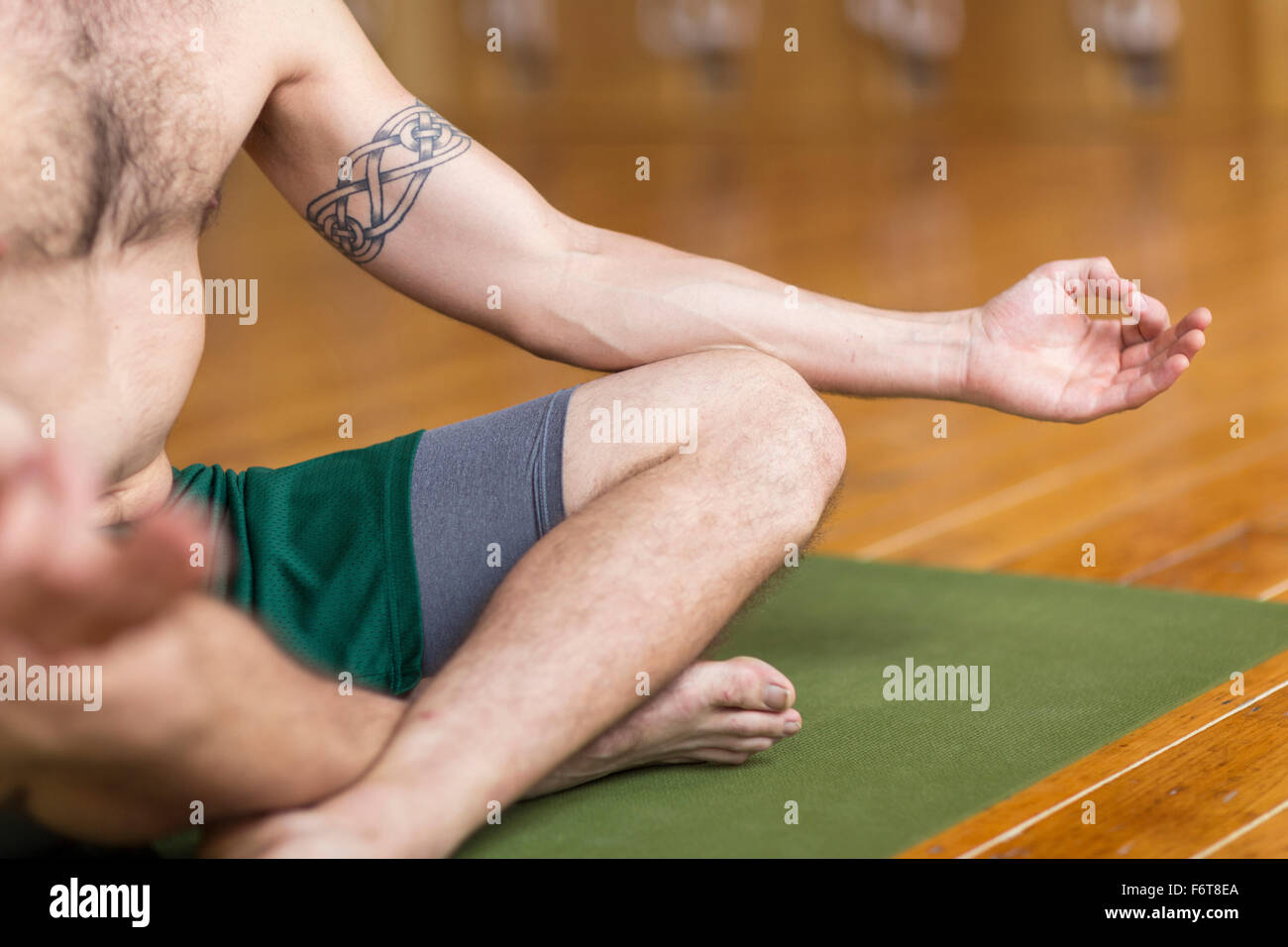 Man practicing yoga in studio - Stock Image