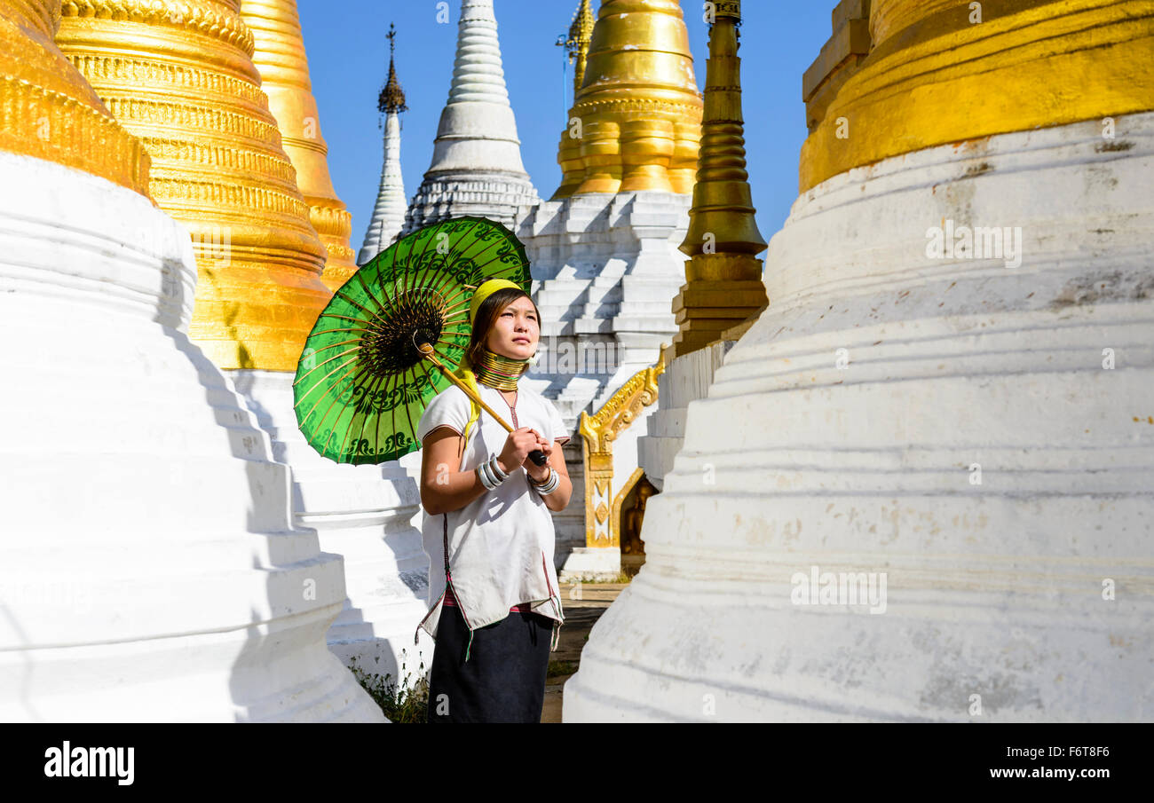 Asian woman carrying parasol at temple - Stock Image