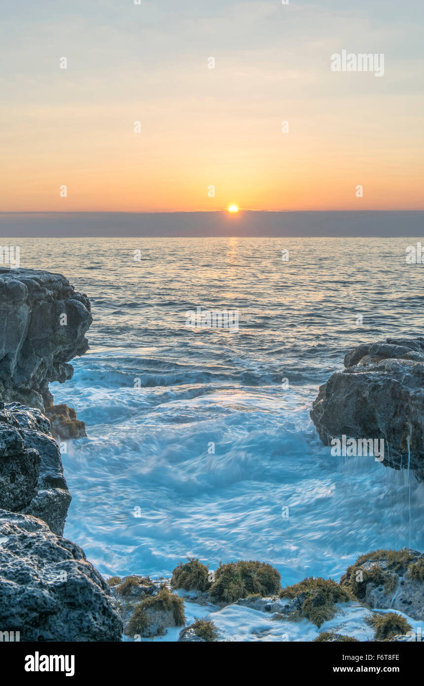 Sunrise over rock formations on beach - Stock Image