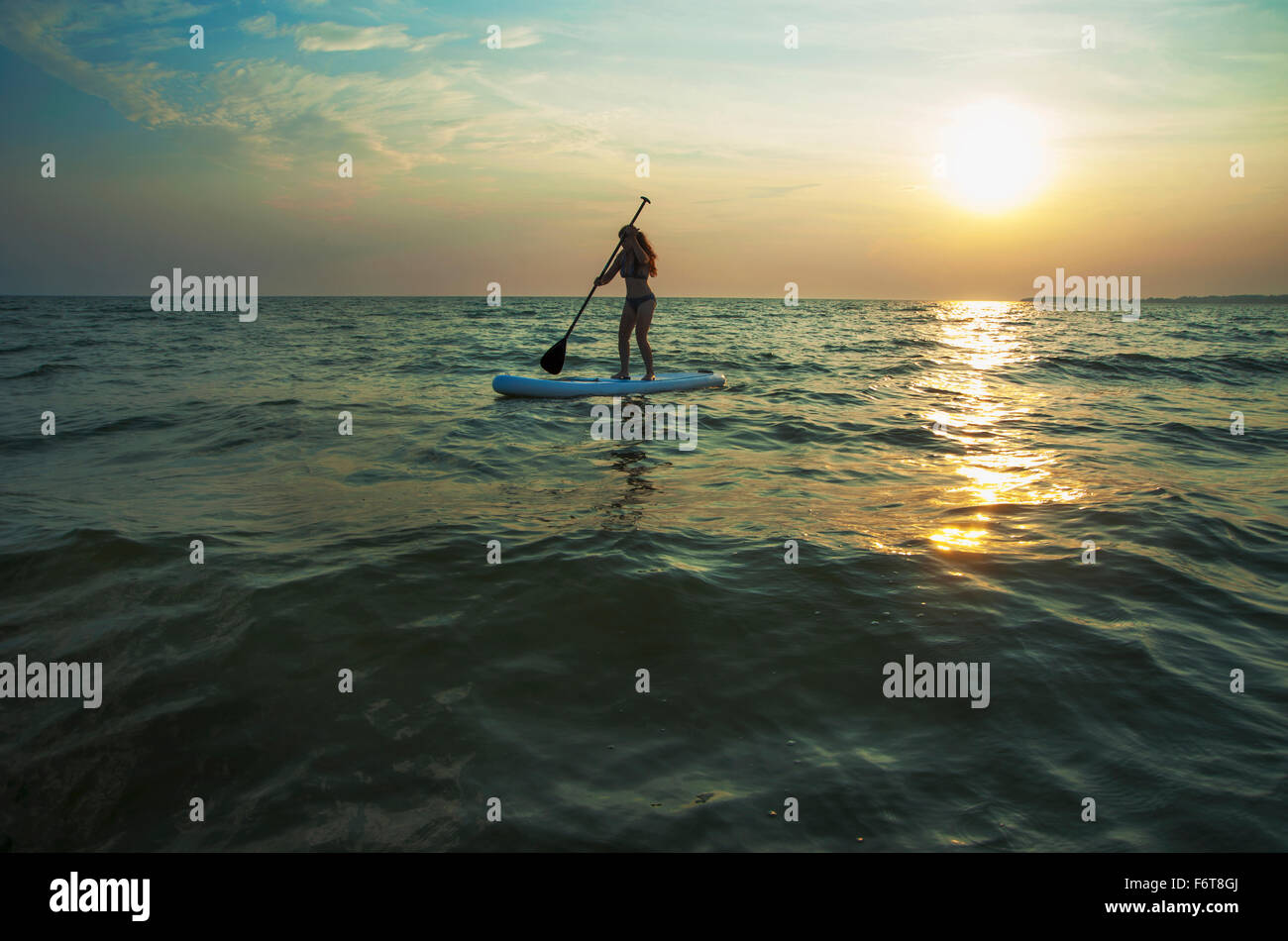 Woman standing on paddleboard in lake - Stock Image