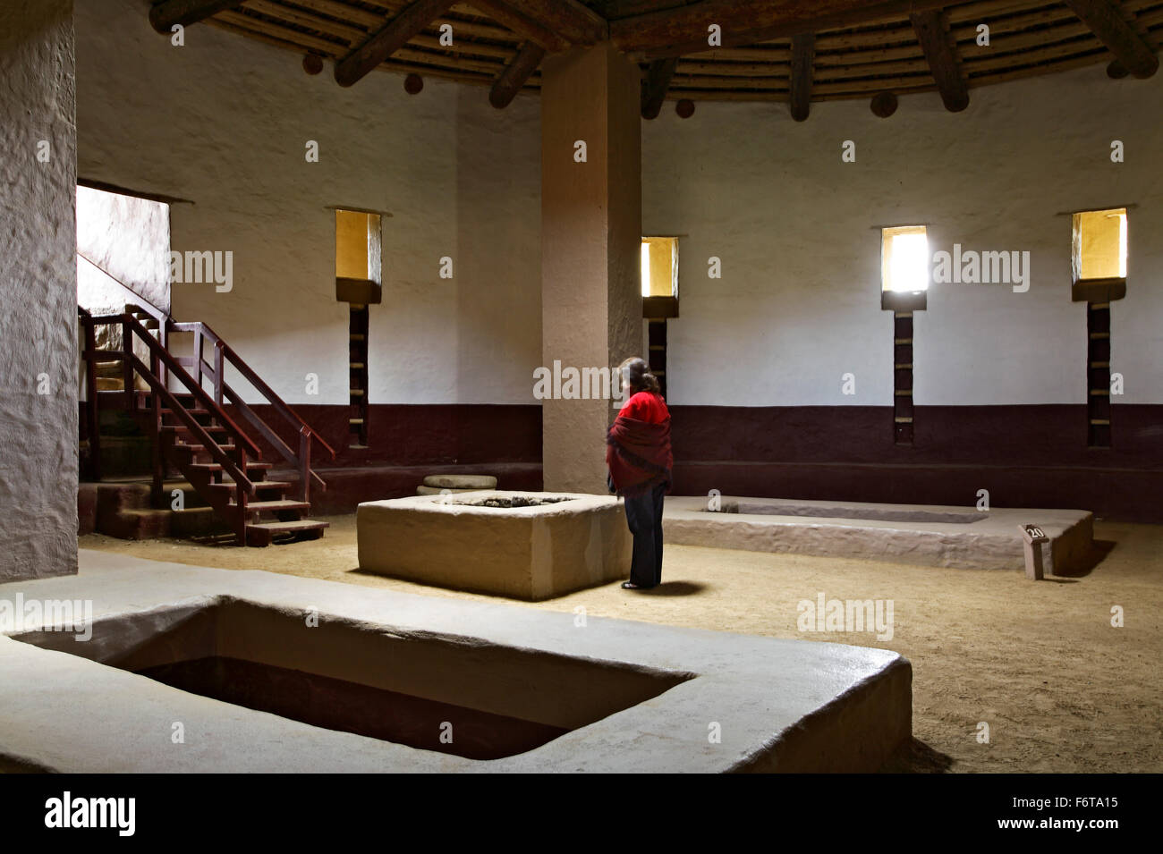 Woman in red sweater, interior of Great Kiva (reconstructed), Aztec Ruins National Monument, Aztec, New Mexico USA - Stock Image