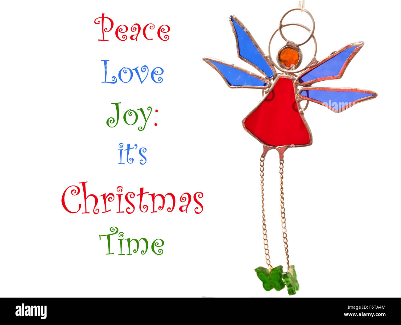 A home made  Christmas glass ornament, a stylised angel swinging in the breeze with text - Stock Image