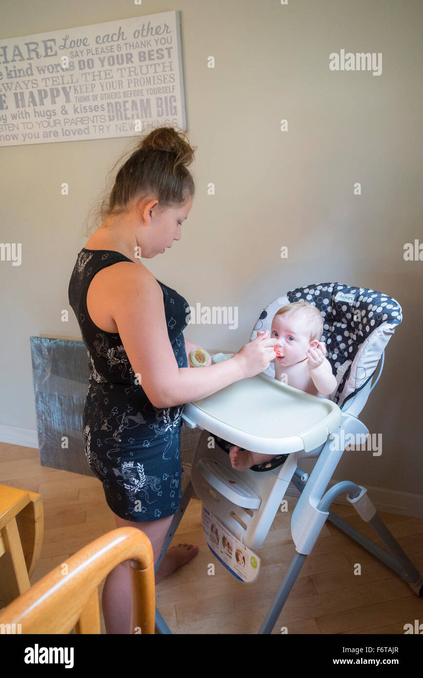 Older sister feeding baby brother in high chair & Older sister feeding baby brother in high chair Stock Photo ...