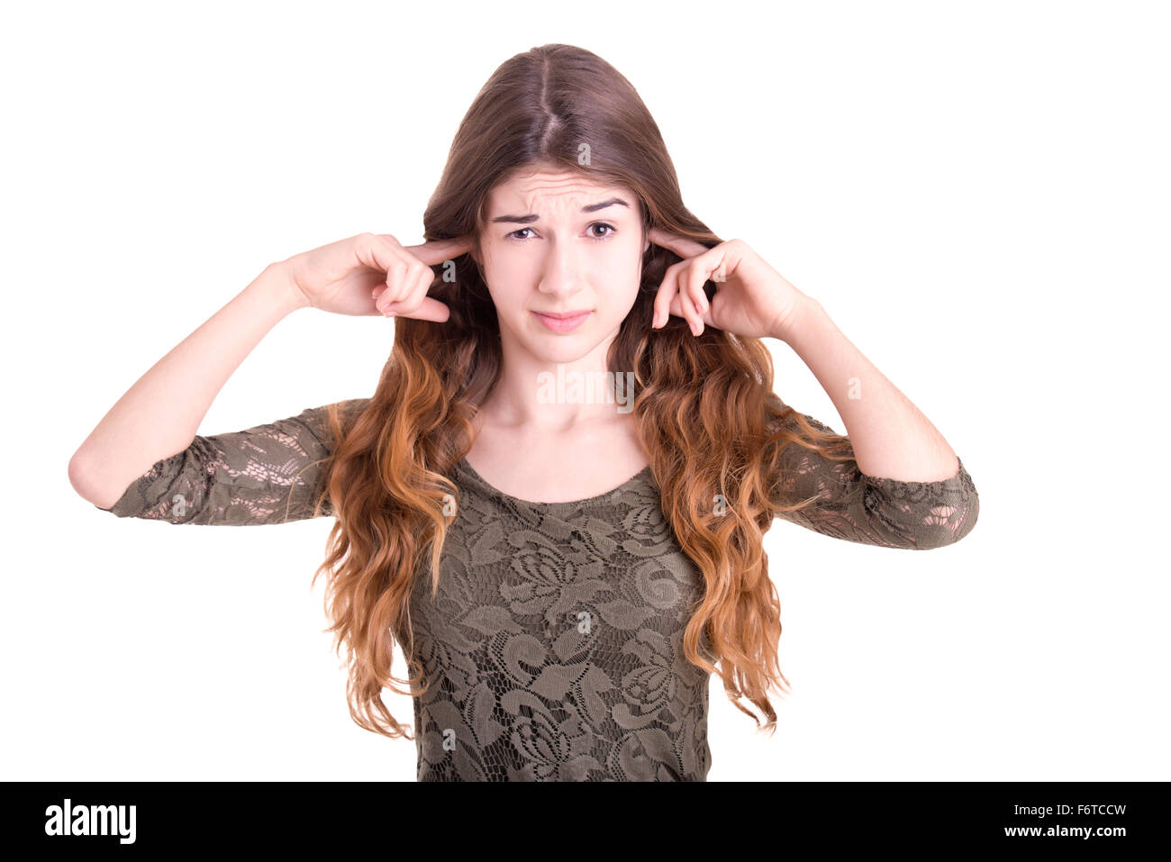 Female with fingers in ears to block sound, isolated in white - Stock Image