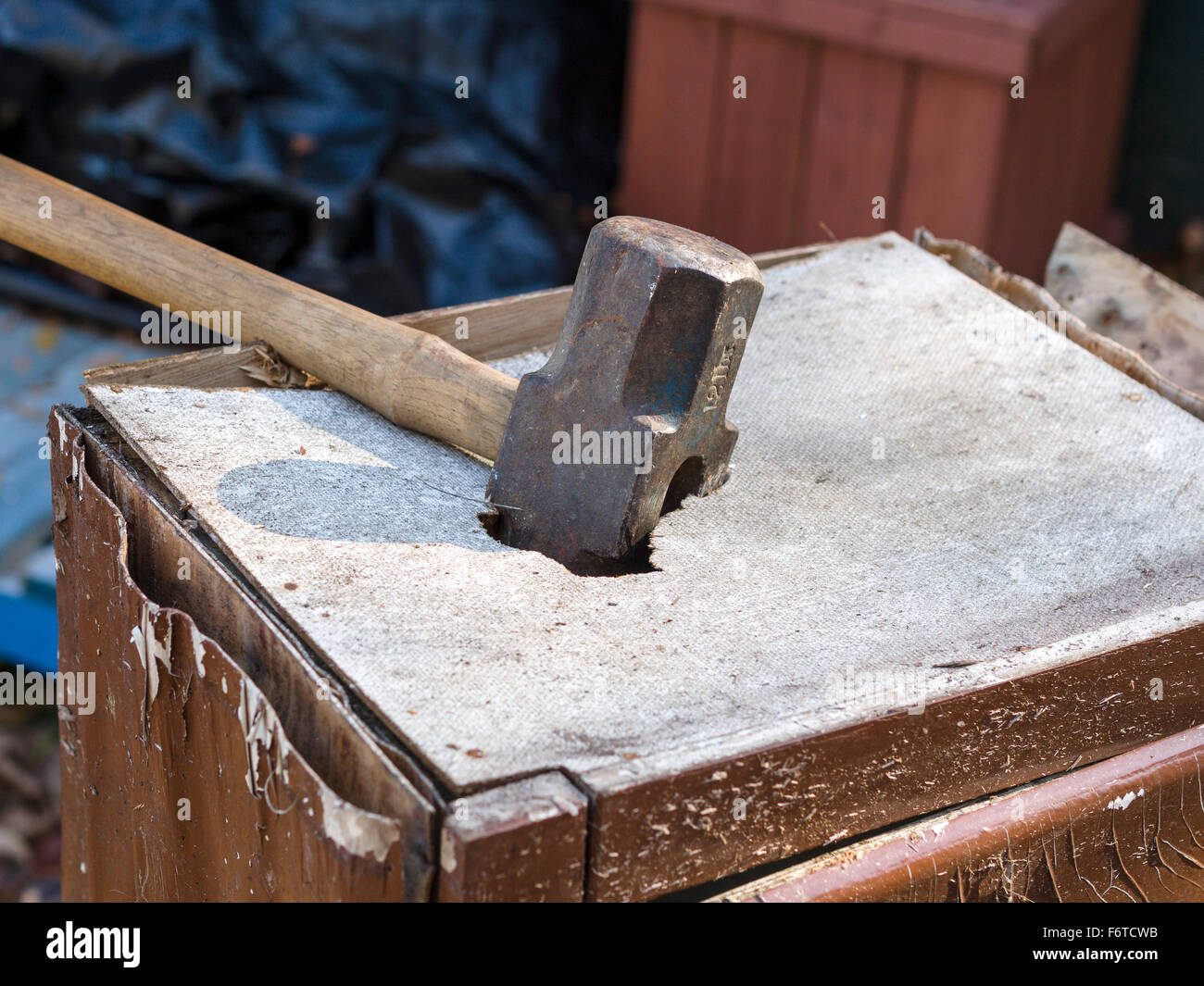 Sledgehammer embedded in a box. A heavy 12 pound sledge hammer smashed into an old worn cupboard box - Stock Image