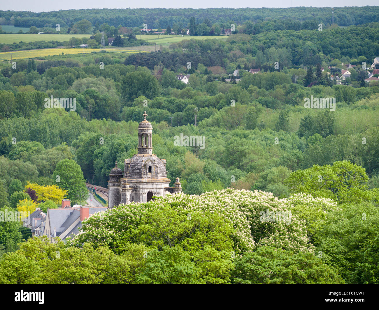 Spire in the Trees near Loches. A stone tower topped with a feur-de-lis pokes above the flowering trees surrounding - Stock Image