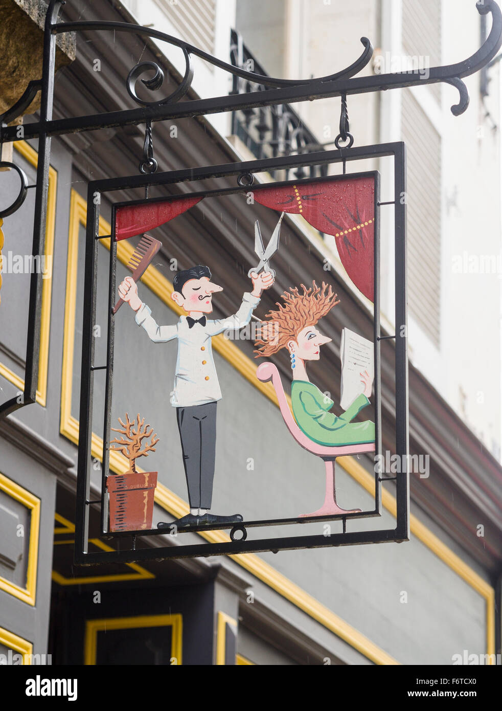 A sign for a Hair Dresser's shop in Loches. A sign depicting a hair stylist and a woman with fly-away hair advertises - Stock Image