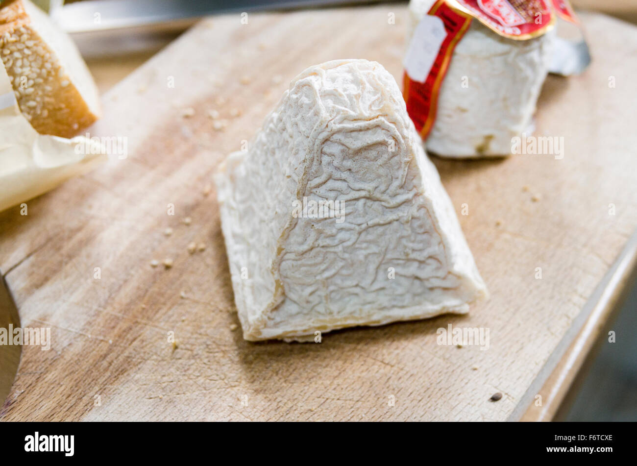 The Wrinkled Rind of a piece of Pouligny St Pierre cheese. A block of cheese on a wooden cutting board. - Stock Image