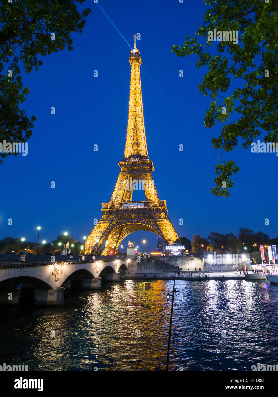 Eiffel's Tower lit at dusk and reflecting in the Seine. A searchlight shines from the top. Paris, Île-de - Stock Image