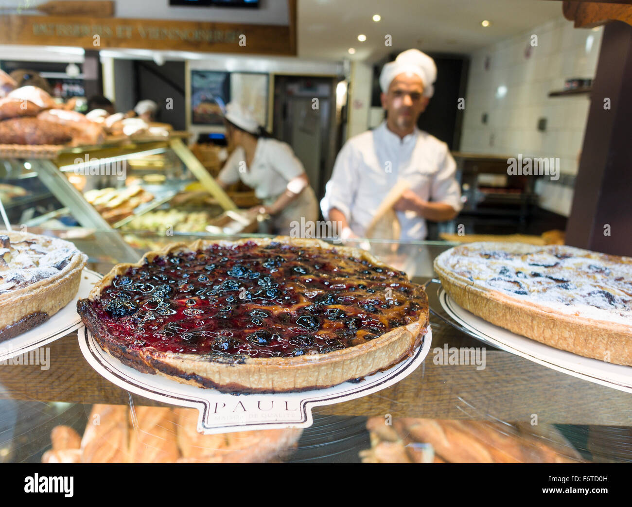 Flan in the Window of Paul Bakery. A well cooked fruit flan graces the window of Paul on the champs-Elysees in Paris. - Stock Image