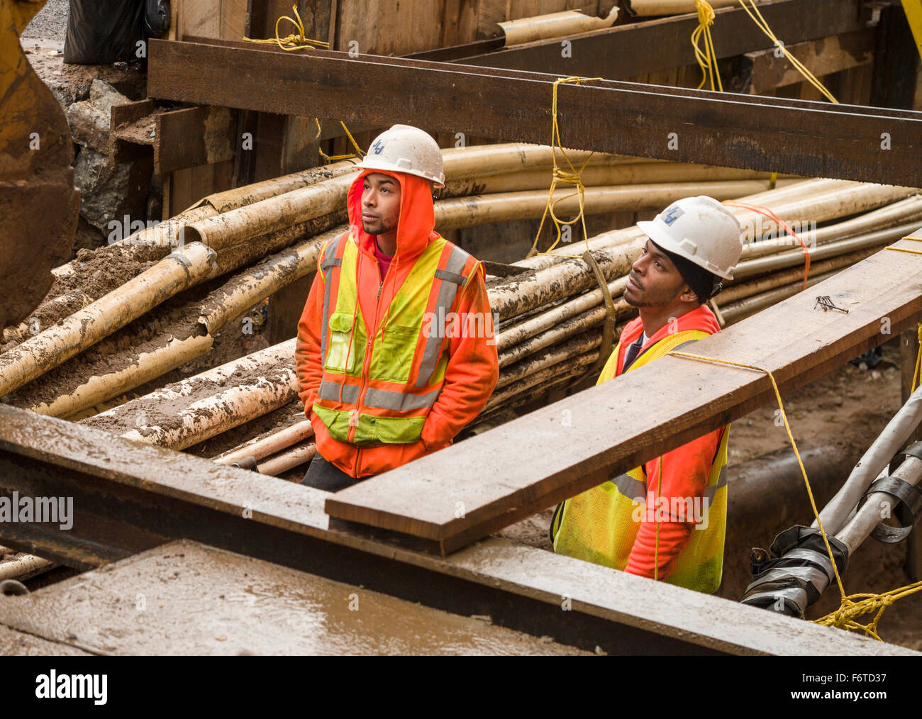 A long wait below street level. Two workers down in a in a damp ditch or excavation filled with pipes waits for - Stock Image