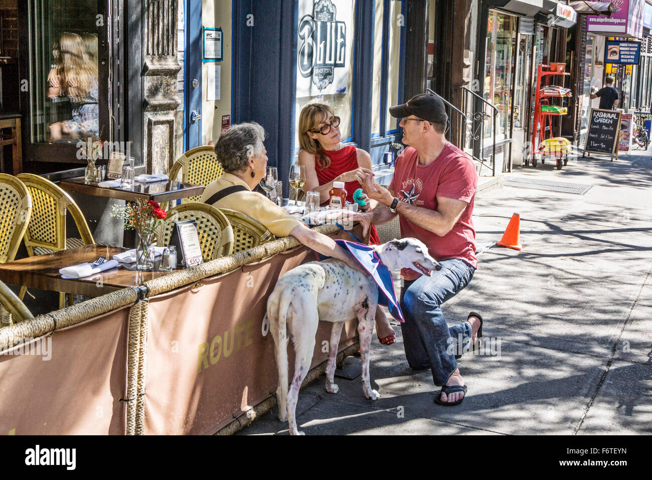 casually dressed man kneels on Ninth avenue sidewalk to chat with with 2 women friends lunching at sidewalk cafe - Stock Image