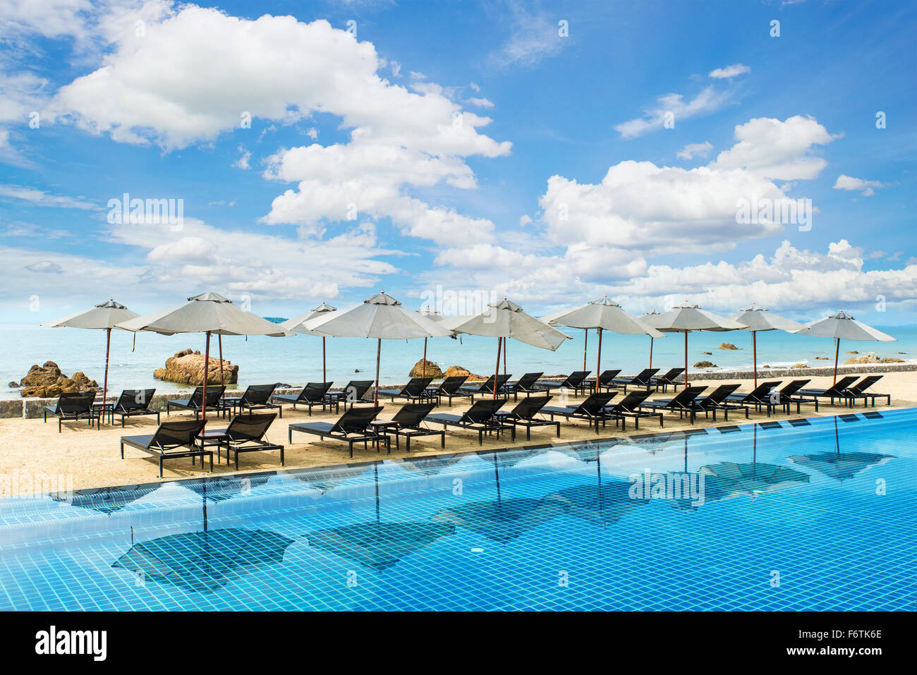 Summer, Travel, Vacation and Holiday concept - Tropical beach resort with lounge chairs and umbrellas in Phuket - Stock Image