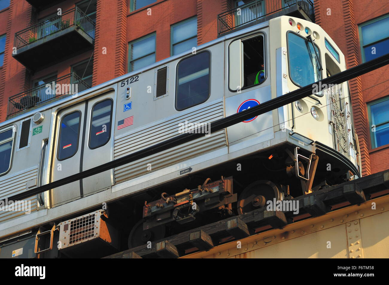 A CTA Green Line rapid transit train passes atop the Lake Street Bridge by converted condominiums as it exits Loop. - Stock Image