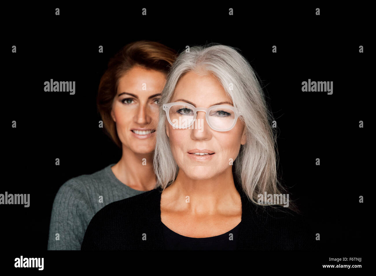 Portrait of mature woman and younger woman standing behind her in front of black background - Stock Image