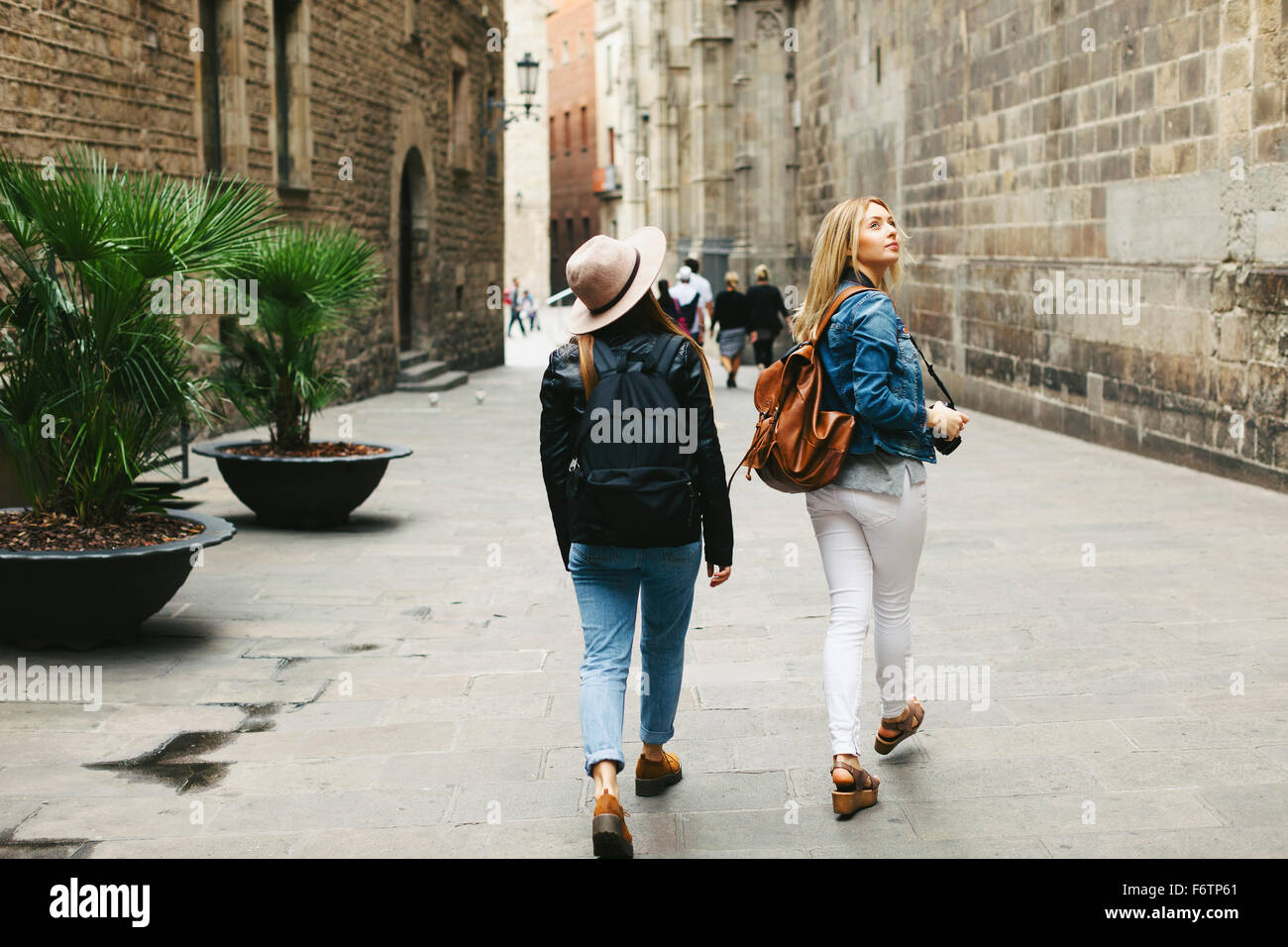 Spain, Barcelona, two young women walking in the city - Stock Image