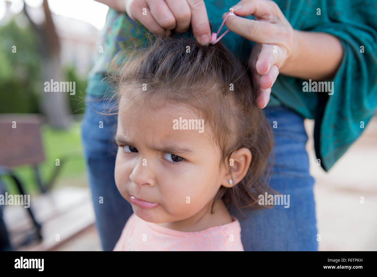 Mother tying up hair of her little daughter, close-up Stock Photo