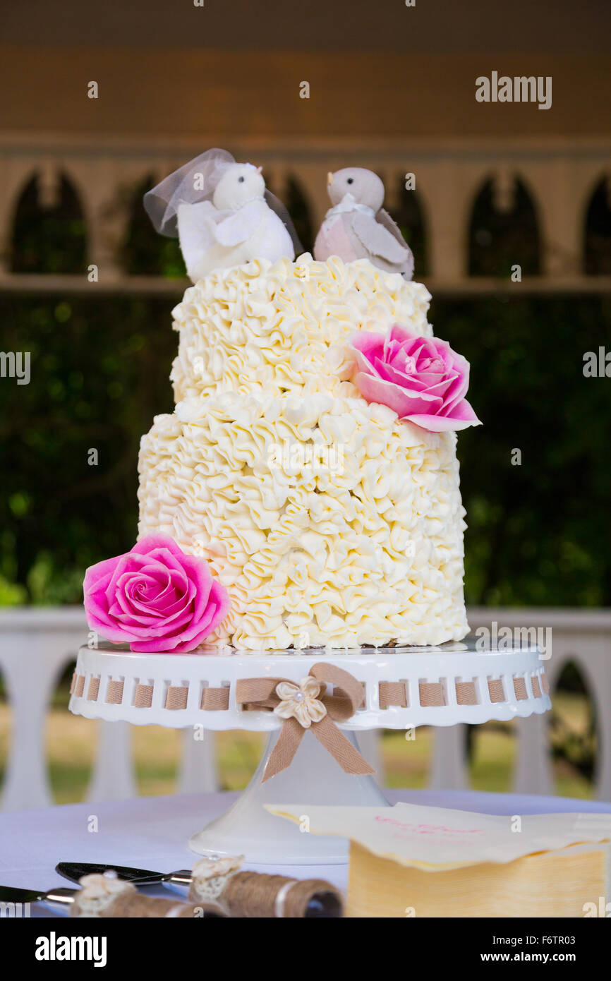 White wedding cake at a reception before the bride and groom cut the ...