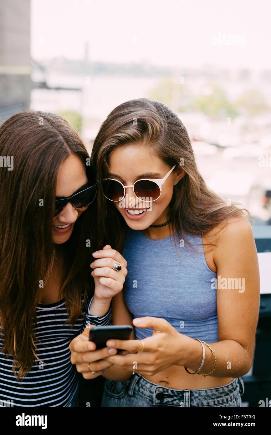 USA, New York City, two smiling friends looking at cell phone - Stock Image