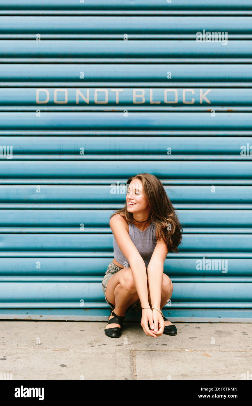 Brunette young woman in front of shutter - Stock Image