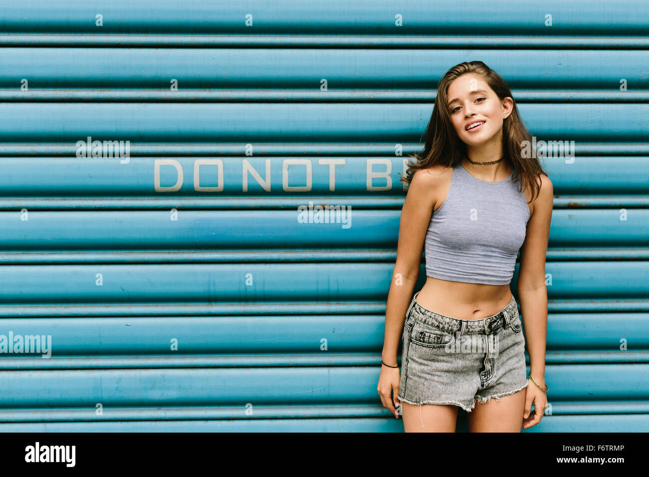 Brunette young woman leaning against shutter - Stock Image