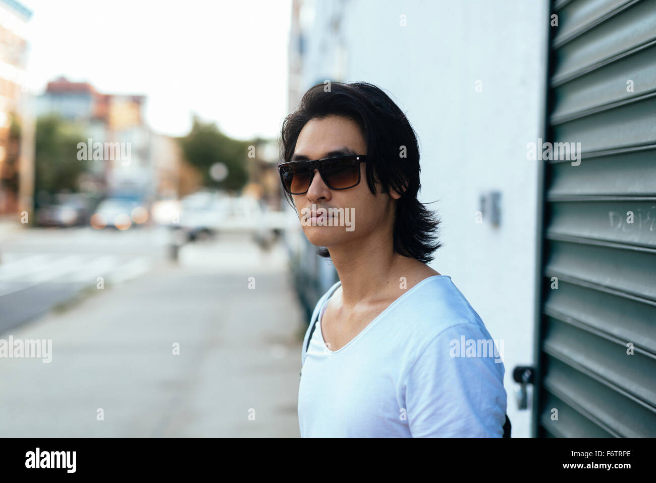 USA, New York City, man standing in front of a shutter - Stock Image