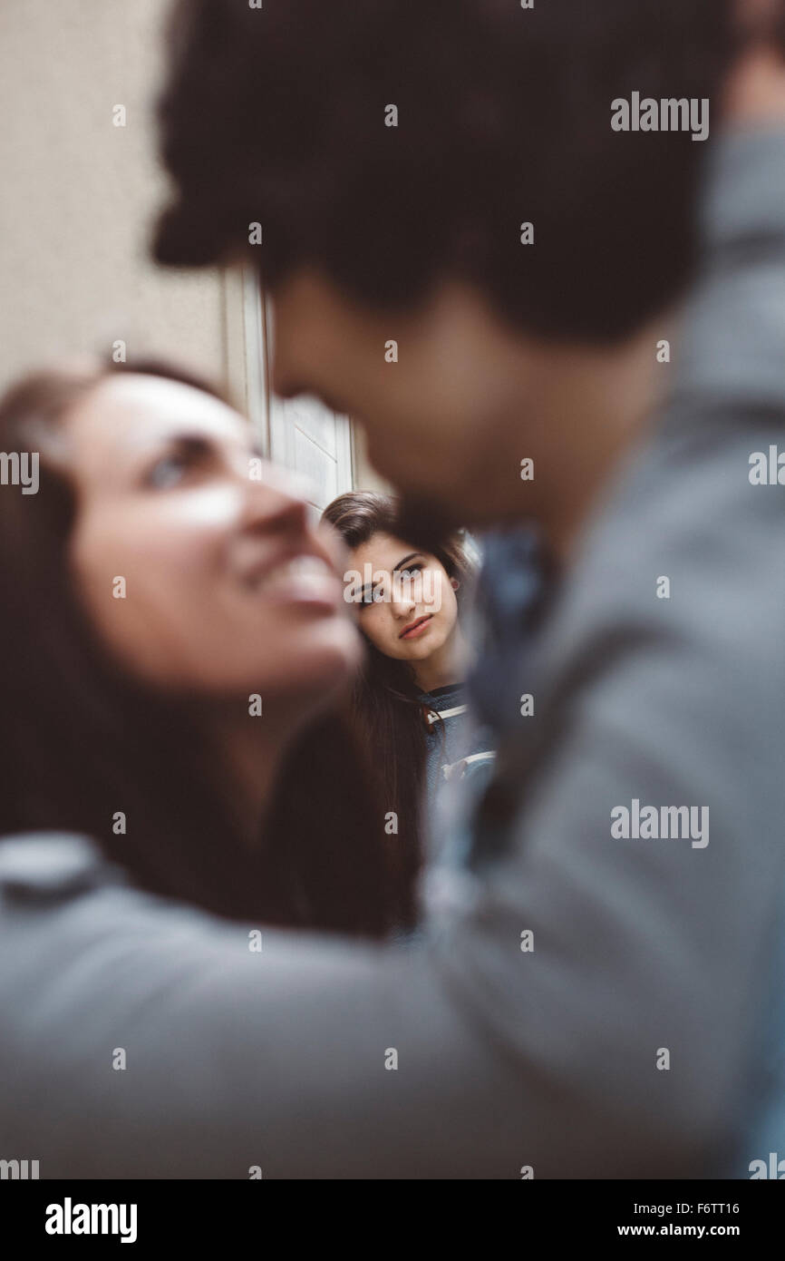 Young couple kissing with another woman looking at them - Stock Image